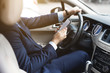 a businessman driving a prestigious car holds a mobile phone in his hand. Hasty life