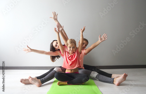 Obraz Young woman having fun with kids doing yoga - fototapety do salonu