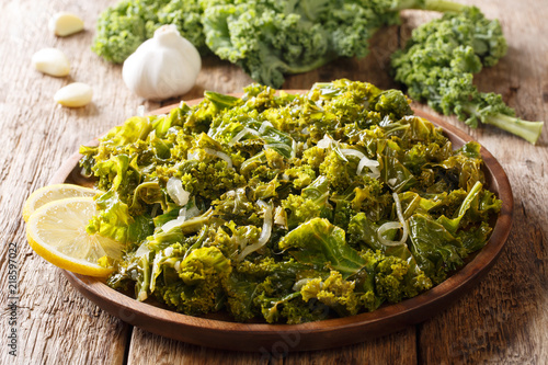 Photo Stands Ready meals Portion kale of leaf cabbage cooked with onions, garlic, oil and lemon close-up on a wooden background. horizontal
