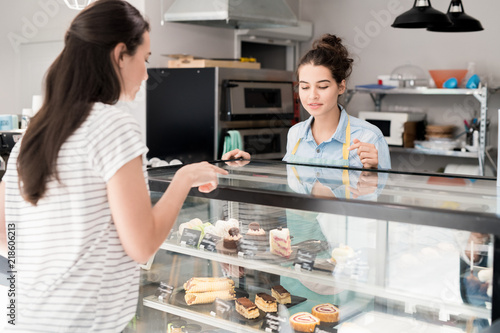 Portrait of modern young woman helping customer choosing desserts in cake shop or coffee house, copy space