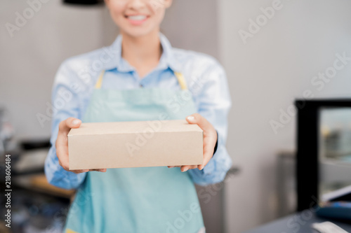 Mid section portrait of unrecognizable woman wearing apron holding box with takeaway food and smiling happily, copy space