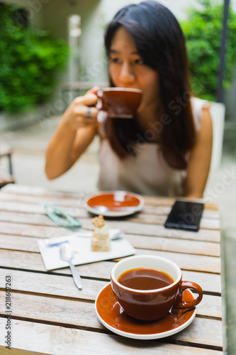 Fotografie, Obraz  Hot americano coffee in the cup with Asian woman drink coffee in the coffee shop