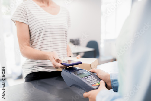 Mid section portrait of modern unrecognizable woman paying by smartphone  via NFC for her order in shop or cafe