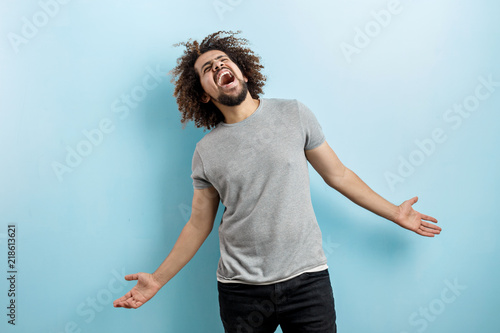 Vászonkép A curly-headed handsome man wearing a gray T-shirt is standing and laughing hard with his hands widly spread, looking upwards over the blue background