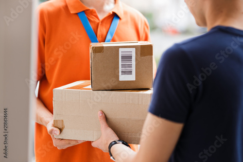 Fotografie, Obraz  A person wearing an orange T-shirt and a name tag is delivering parcels to a client
