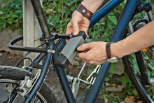 A Man Opens A Bicycle Lock