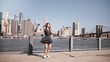 Back view of girl with hair blowing in the wind spinning at beautiful Manhattan skyline view, arms open slow motion.
