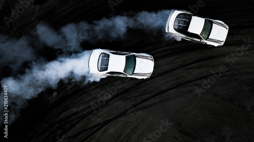 Cuadros en Lienzo Aerial top view two cars drifting battle on asphalt race track, Two cars battle drift, Race cars view from above, Auto or automobile vehicle activity background concept
