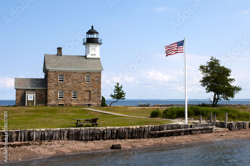 American Flag Flying Near Stone Lighthouse in Connecticut