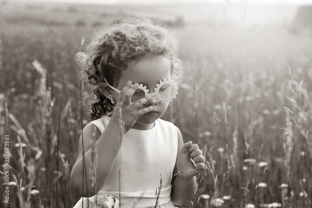 Fototapeta Little girl with curls in pink glasses in a field at sunset. A child in nature. Black and white photography