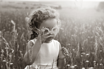 Little girl with curls in pink glasses in a field at sunset. A child in nature. Black and white photography