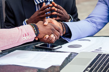 Close Up Hands Of Group Three Stylish African American Businessman Friends Handshaking In A Summer Cafe Outdoors. Concept Of Successful Good Deal
