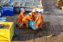 Offshore Workers Preps Oil Drum On Cargo Net On A Construction Barge At Oilfield