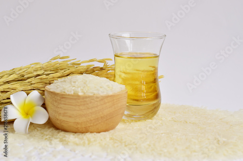 Tablou Canvas Rice bran oil in a glass with uncooked jasmine rice in a wooden bowl and ear of
