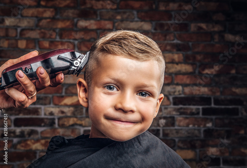 Fotografie, Obraz  Close-up portrait of a cute smiling boy getting haircut against a brick wall