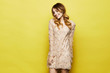 canvas print picture - Fashionable and emotional blonde model girl with bright makeup and with shiny smile, in stylish peach dress posing in studio at yellow background
