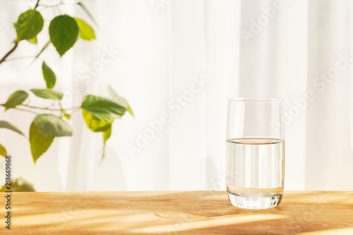 glass of water on wooden table, sunny morning, copy space for your text