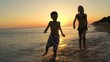Happy children playing on the beach at the sunset time. Two Kids having fun outdoors. Concept of summer vacation and friendly family.