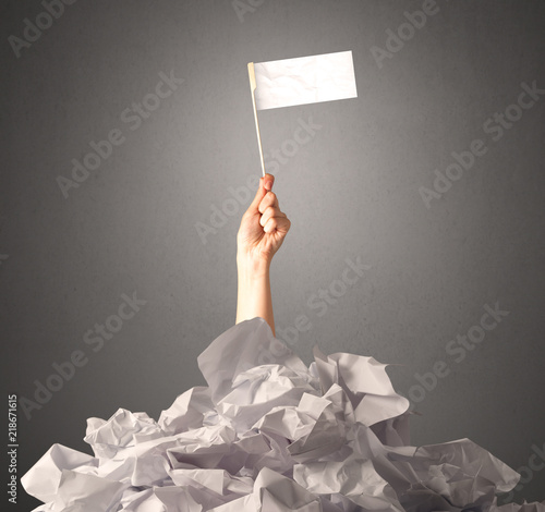Fotografía  Female hand emerging from crumpled paper pile holding a white blank flag