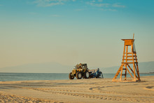 Tractor Cleaning The Beach On A Calm Morning At The Beach With A Safeguard Post On A Sunny Morning With Olympus Mountain And Clear Sky In The Background.