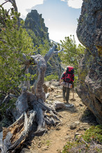 Backpacking Man Leads Down A Trail Made Of Rock In The Idaho Wilderness