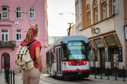 Tourist woman looking at passing tram in ancient city Olomouc, Czech Republic