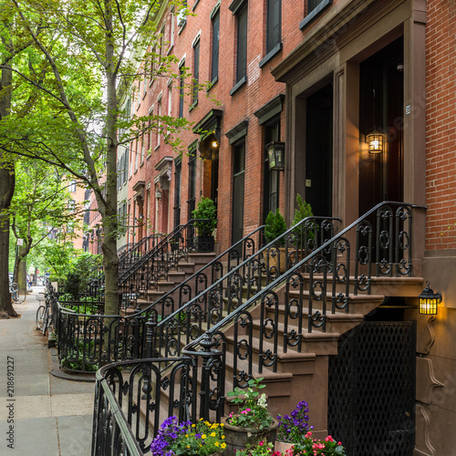 Row of old brownstone buildings along an empty sidewalk block in the Greenwich Village neighborhood of Manhattan, New York City, NYC, USA.