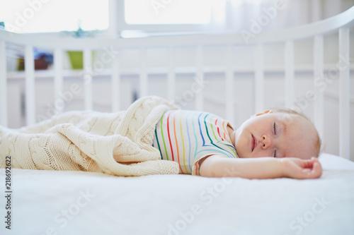 Foto  Baby girl sleeping in co-sleeper crib