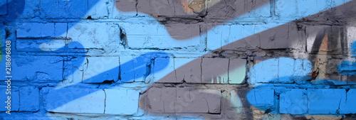 Naklejka premium Fragment rysunków graffiti. Stara ściana ozdobiona plamami farby w stylu kultury ulicznej. Kolorowa tło tekstura