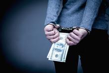 Woman Handcuffed For Her Crimes With US Dollars In Her Hands As Symbol Of Corruption And Bribe
