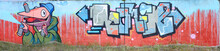Full And Acomplished Graffiti Artwork. The Old Wall Decorated With Paint Stains In The Style Of Street Art Culture. Colored Background Texture