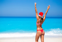 Beautiful Young Woman With Santa Hat On The Beach Looking Into The Ocean