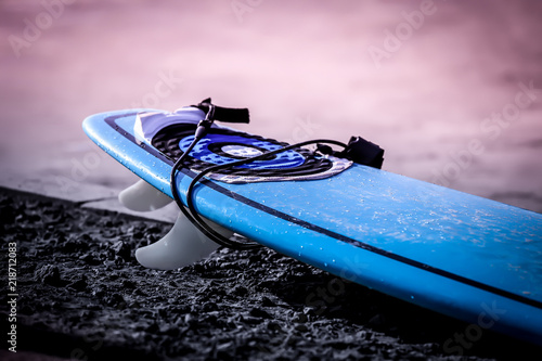 Foto op Aluminium Oceanië new surfboard on the coastline at sunrise on the ocean. blue surf board laying on the coastline waiting for surfers.