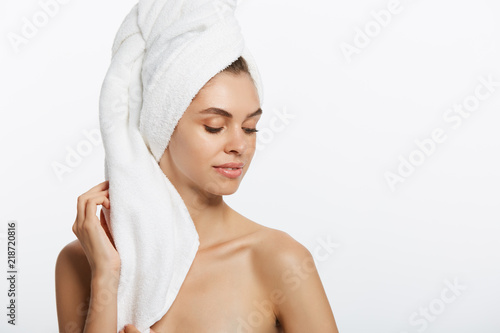 Fototapeta Spa and beauty concept - happy young girl with clean skin and with a white towel on her head washes face obraz na płótnie