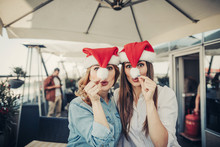 Fooling Around. Lovely Ladies In Santa Claus Hats Celebrating New Year At Cozy Cafe While Bearded Man Checking Mobile Phone On Blurred Background