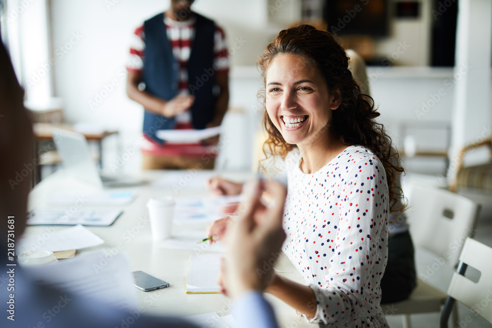 Fototapety, obrazy: Happy young businesswoman sitting at desk and communicating with her colleagues during a meeting