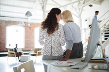 Rear View Of Two Businesswomen Whispering While Sitting At Workplace At Modern Office