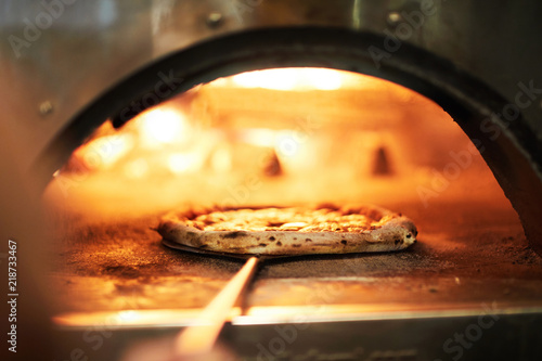 Special tray with handle with raw pizza inside oven for roasting on fire