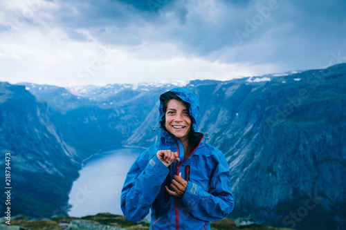 Fotografía Happy woman zip up blue sportive jacket before rain, get ready for adventure and smiling in cliff during trip Norway