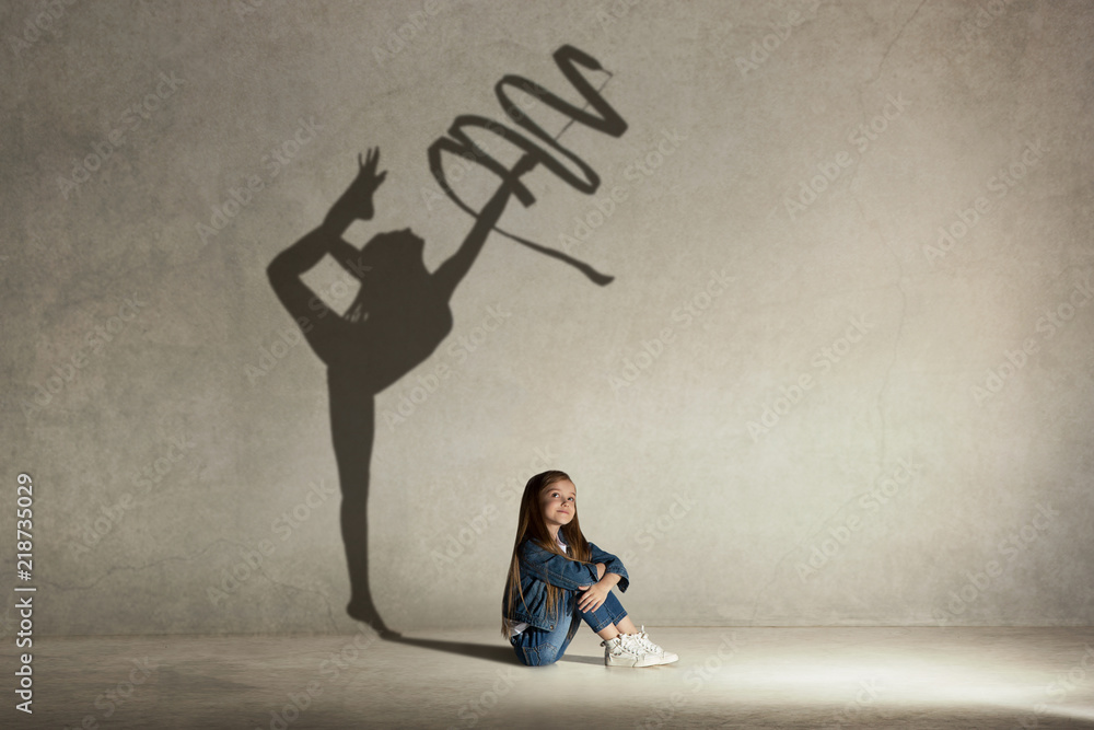 Fototapeta Baby girl dreaming about gymnast profession. Childhood and dream concept. Conceptual image with shadow of female gymnast on the studio wall