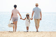 Young family of three going to have picnic by seaside on hot summer day or during vacation