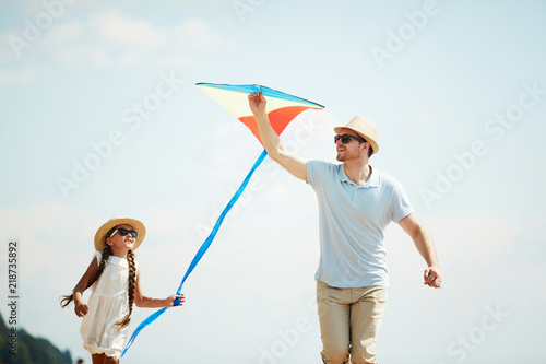 Little girl and her father playing with self-made kite against blue sky on summer day