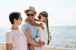 Happy young family consisting of father, mother and cute little daughter laughing and enjoying chill by seaside