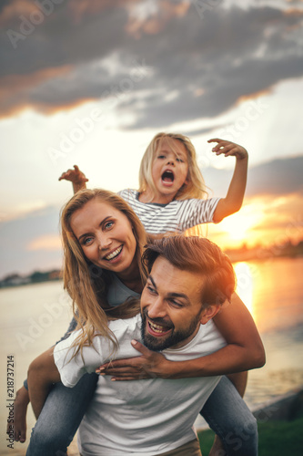 Portrait of happy unshaven husband spending tie with cheerful wife and satisfied female child in nature