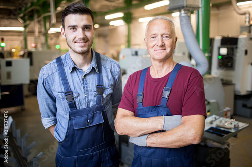 Portrait of two mechanics in overalls standing at his workplace at manufacturing plant with lathe in the background