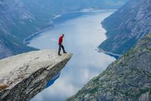 Man In Blue Sportswear Standing On Trolltunga In Norway.