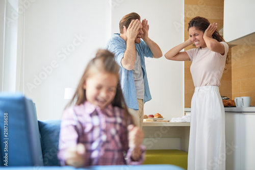 Fotografie, Tablou  Stressed parents covering their ears in horror while their daughter shouting lou