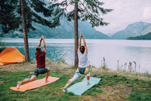 Back View Of Sporty Couple Near Orange Tent With Their Hands Apart Against The Background Of Lake And Mountains. The Man And Woman Workout Yoga With Mats At Camping In Summer Norwegian Cloudy Morning.