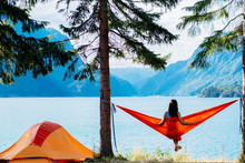 Back View Of Young Woman Silhouette Relaxing On Orange Hammock Between Two Trees Pine Enjoying The View At The Lake In Summer Norwegian Cloudy Morning.