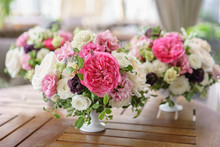 Arrangement Of Fresh Flowers In Pastel Colors. Wedding Background. Table In A Restaurant. Different Varieties Of Garden And Shrub Roses In A Light Vase On Wooden Table